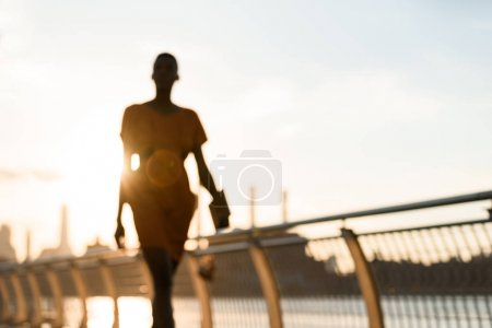 Young african american fashionable business woman walking along the pier with New York city view