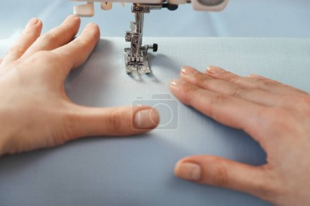 Hands of tailor pushing fabrics while sewing