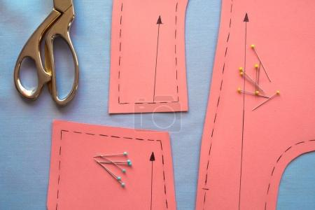 Sewing pattern on fabrics ready to cut surrounded with tailor's tools