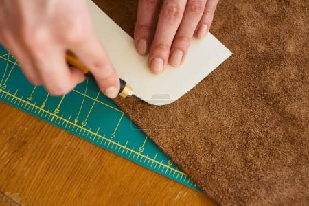 Artisan cutting leather with stencil knife