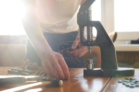 Leather artisan working on manual machine