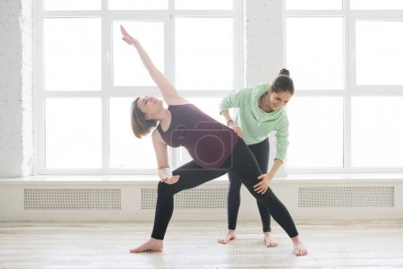 Photo for Personal yoga instructor assisting pregnant woman student - Royalty Free Image