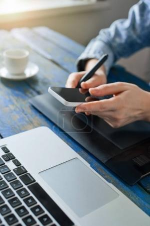 Photo pour Personne qui utilise le téléphone tout en travaillant sur ordinateur et tablette graphique - image libre de droit