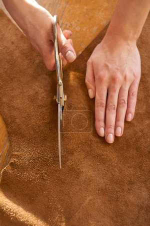 Tailor cutting leather with scissors
