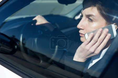 Business lady talking on the phone in the car