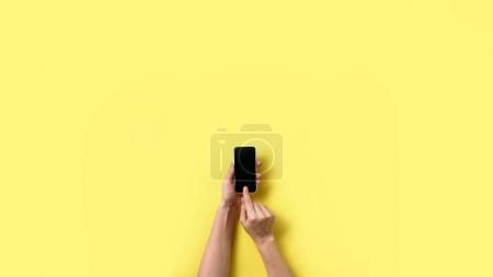 Hands using smart phone on yellow