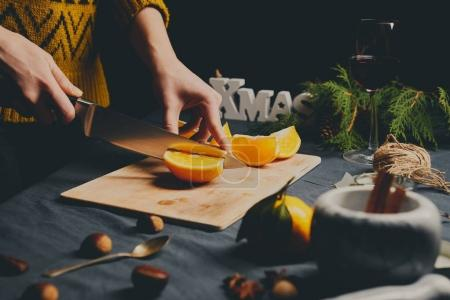 Female hands cooking orange jam for Christmas gifts