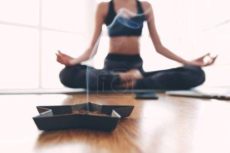 Photo pour Pleine prise de corps d'une jeune femme minuscule méditant assise sur un tapis devant une grande fenêtre lumineuse, brûlant des bâtons parfumés. Elle porte un char et un pantalon foncé. - image libre de droit
