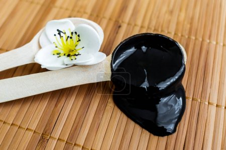 The black substance in a wooden spoon on a background of bamboo. Black mask