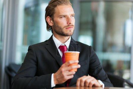 Handsome businessman having coffee