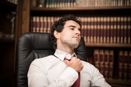 Businessman relaxing and loosening necktie