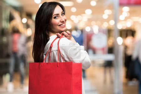 Photo for Smiling woman holding a shopping bag in a shopping mall - Royalty Free Image