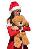 Ragazza di Santa Claus che tiene teddy bear