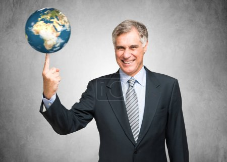 Businessman spinning a globe on finger