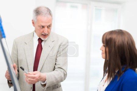 Senior businessman explaining to businesswoman