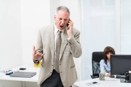 Angry businessman yelling on phone