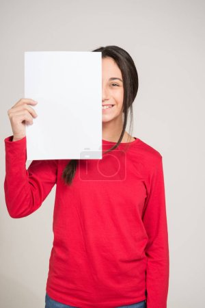 Teen covering face with paper