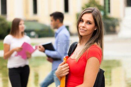 Photo pour Portrait d'étudiante souriante, groupe de camarades de classe en arrière-plan - image libre de droit