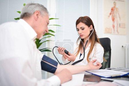 Photo pour Médecin cheking une pression artérielle patient - image libre de droit
