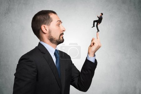 Big businessman keeping smaller one on fingertip