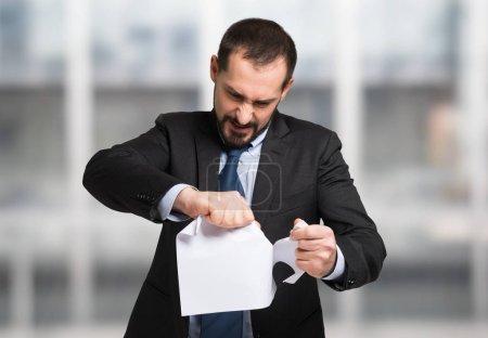 Photo pour Homme d'affaires en colère déchirant un document - image libre de droit