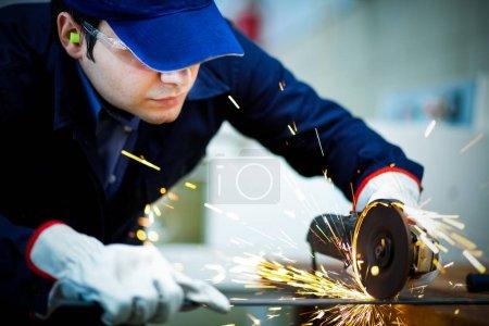 Worker grinding metal plate