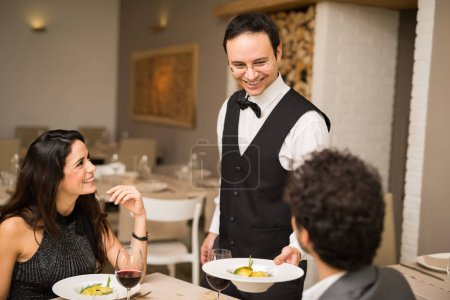 Waiter serving two customers