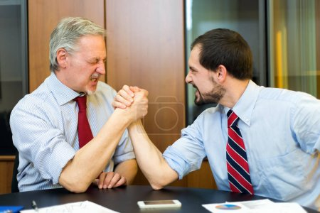 Business people doing arm wresling