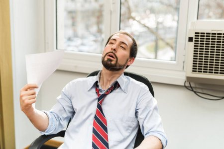 Photo for Businessman suffered from broken air conditioner, the office is too hot - Royalty Free Image