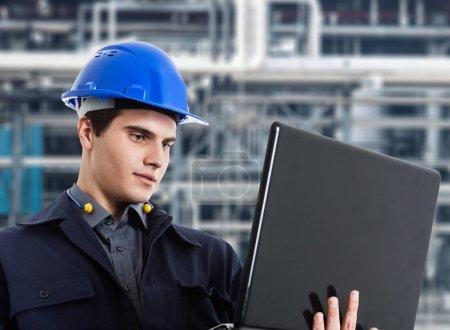 Photo pour Ingénieur utilisant un ordinateur portable devant une usine industrielle - image libre de droit