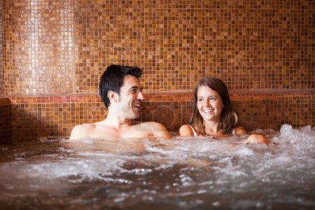 Beautiful couple doing a whirlpool bath in a spa...
