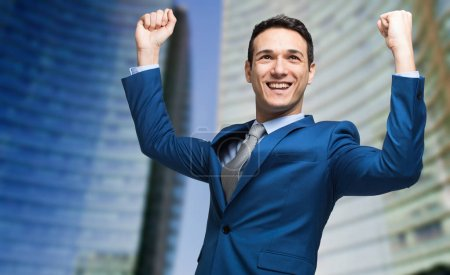 businessman raising arms in sign of victory