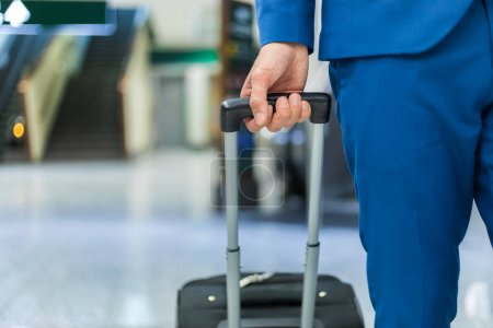 Businessman pulling trolley in an airport