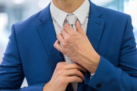 handsome businessman adjusting tie