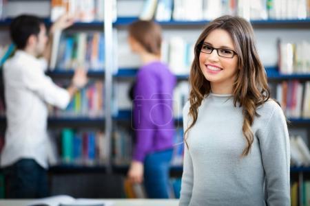 Photo pour Groupe d'étudiants qui étudient dans une bibliothèque - image libre de droit