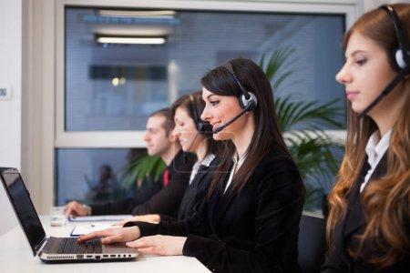 Photo pour Groupe de femmes parlant sur les écouteurs dans leur bureau - image libre de droit