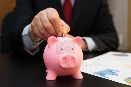 Photo pour Gros plan d'un homme d'affaires qui met de l'argent dans une tirelire - image libre de droit