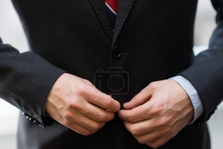 Photo pour Détail d'un homme d'affaires boutonnage devant vers le haut de son costume - image libre de droit