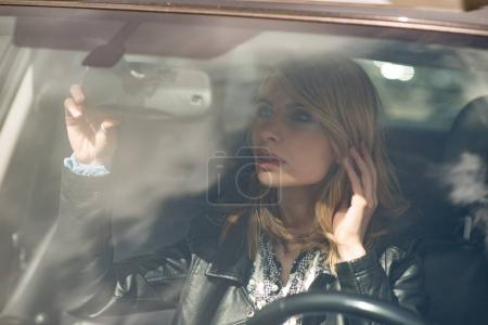 Woman looking at herself through car mirror