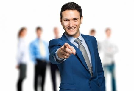 businessman pointing at camera in front of team