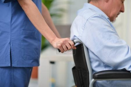 nurse pushing wheelchair with man