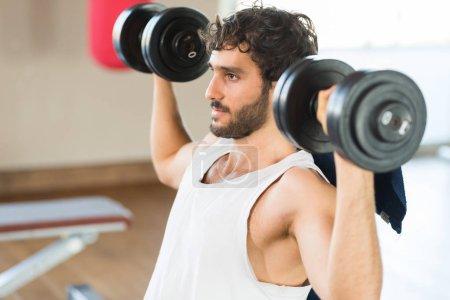 Bodybuilder lifting dumbbells in a gym