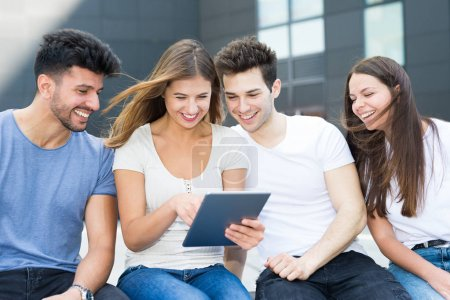 Sitting group of friends using a tablet