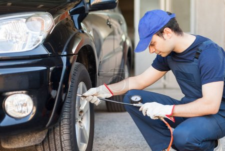 Mechanic checking the pressure of a tire