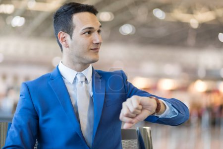 Photo pour Homme d'affaires, temps d'enregistrement à l'aéroport, concept de retard de vol - image libre de droit