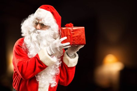 Photo for Indoor portrait of Santa Claus holding a present - Royalty Free Image