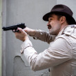 Detective taking cover and aiming with his handgun...