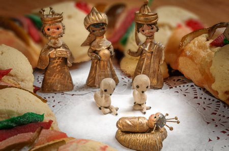 Photo pour Epiphany Cake, gâteau des rois ou Rosca de reyes avec mangeoire sur table en bois - image libre de droit