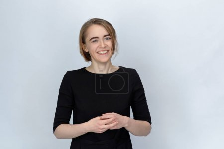 Studio portrait of a young woman with a wide smile and narrowed