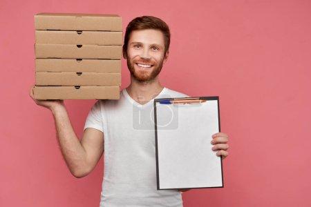 Photo pour Courier aux cheveux de gingembre blonds et à la barbe, vêtu d'un t-shirt blanc décontracté, tenant de nombreuses boîtes à pizza isolées sur fond rose au Studio. comprimé avec clip sur lequel se trouve la forme vierge pour la publicité - image libre de droit